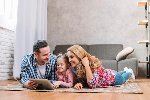 Glückliche familie, die auf teppich unter verwendung der digitalen tablette liegt Kostenlose Fotos