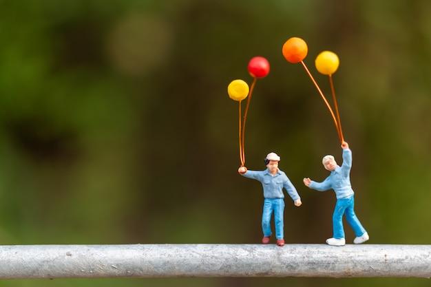 Glückliche familie, die bunte ballone hält Premium Fotos