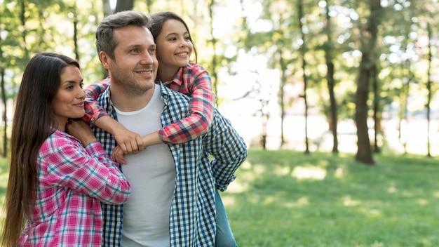 Glückliche familie, die das karierte musterhemd steht im park weg schaut trägt Premium Fotos