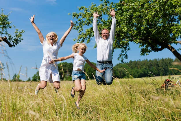 Glückliche familie, die draußen in die sonne springt Premium Fotos