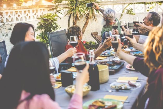 Glückliche familie, die ein selfie-foto mit smartphone-kamera beim grillabendessen im hinterhof des hauses macht Premium Fotos