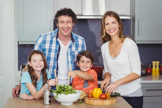 Glückliche familie, die einen gemüsesalat zubereitet Premium Fotos