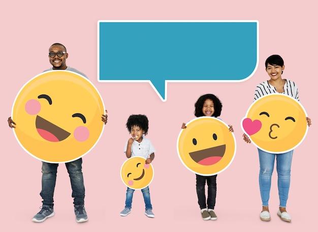Glückliche familie, die emoji-ikonen hält Kostenlose Fotos