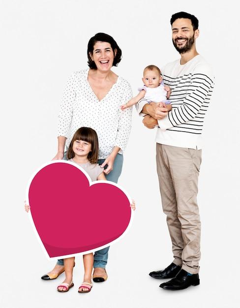 Glückliche familie, die herat geformte ikone hält Kostenlose Fotos