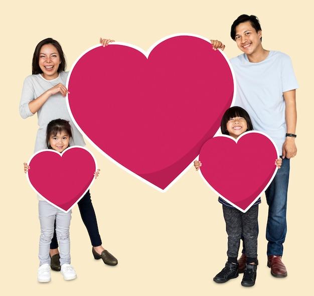 Glückliche familie, die herzikonen hält Premium Fotos