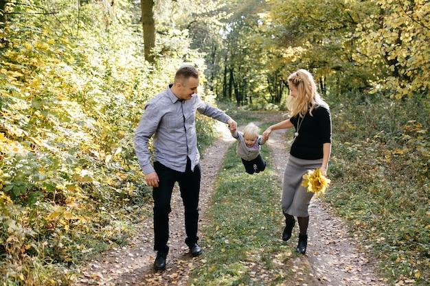 Glückliche familie, die im herbstpark spielt und lacht Kostenlose Fotos
