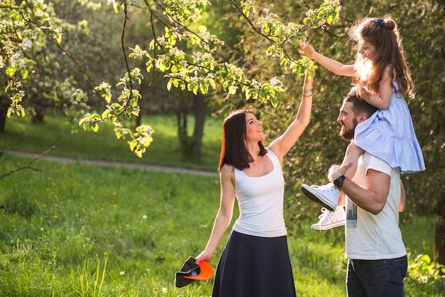 Glückliche familie, die im park genießt Kostenlose Fotos