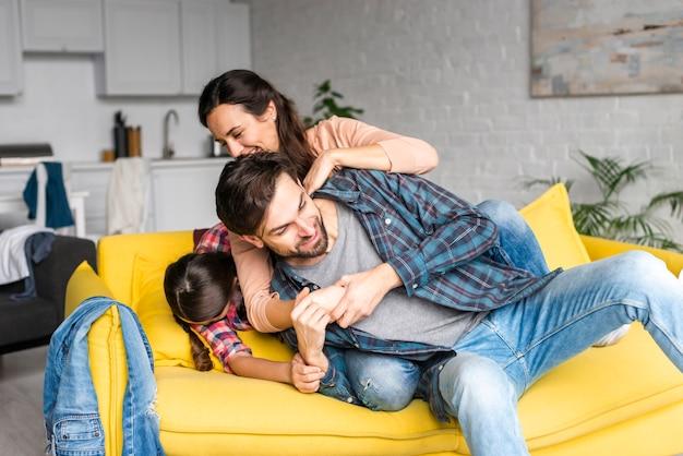 Glückliche familie, die im wohnzimmer herumalbert Kostenlose Fotos