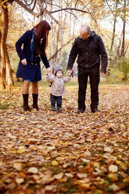 Glückliche familie, die in autumn park geht Premium Fotos