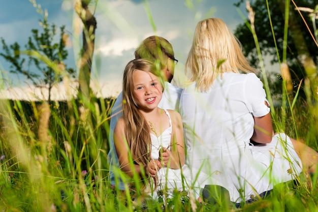 Glückliche familie, die in der wiese sitzt Premium Fotos
