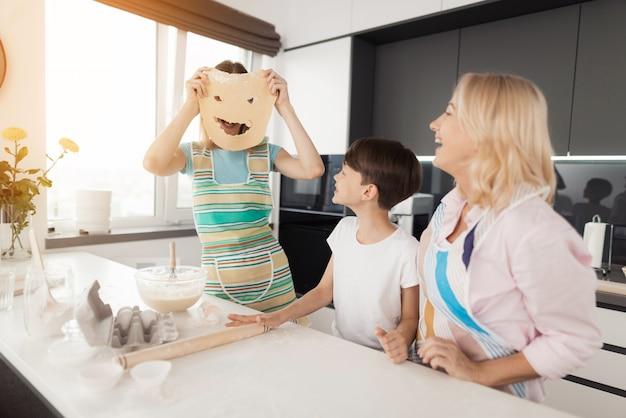 Glückliche familie, die kocht. frau stellen gesicht heraus teig her. Premium Fotos