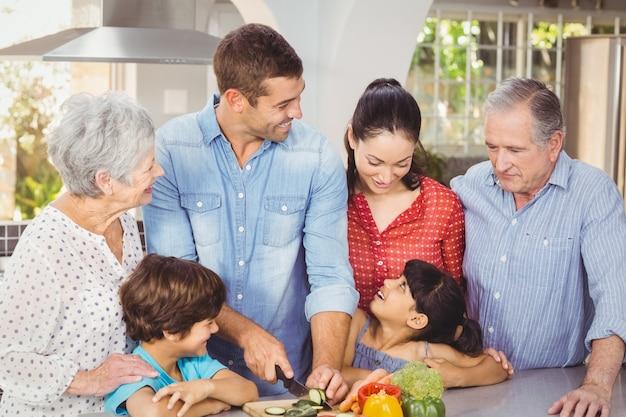 Glückliche familie, die lebensmittel in der küche zubereitet Premium Fotos