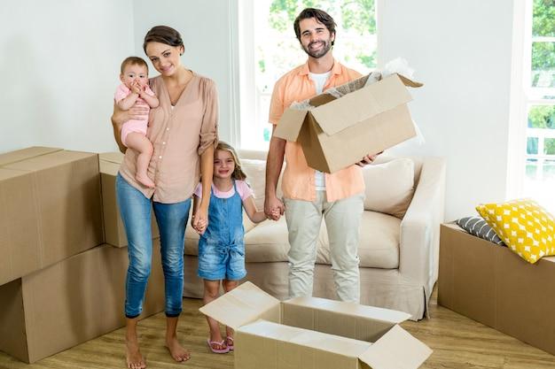 Glückliche familie, die mit kästen im neuen haus steht Premium Fotos