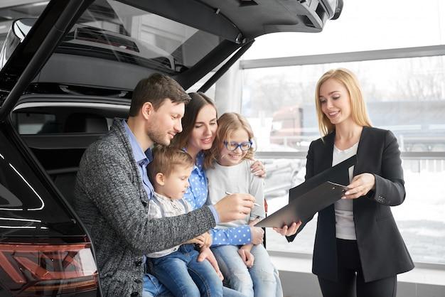 Glückliche familie, die neues bequemes schwarzes auto im selbstsalon kauft Premium Fotos