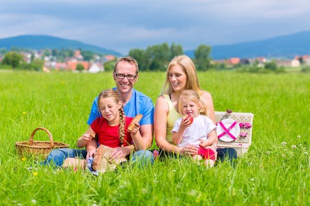 Glückliche familie, die picknick in der wiese hat Premium Fotos