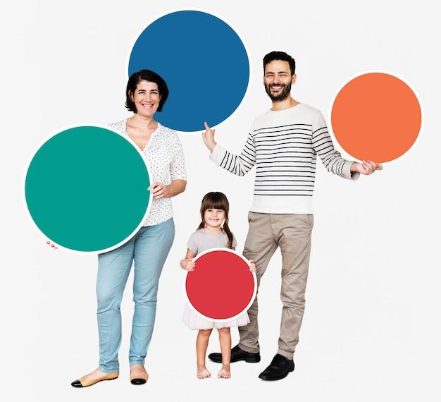 Glückliche familie, die runde bunte bretter hält Kostenlose Fotos