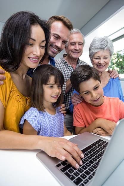 Glückliche familie, die unter verwendung des laptops aufeinander einwirkt Premium Fotos