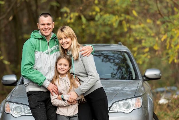 Glückliche familie, die vor auto aufwirft Kostenlose Fotos