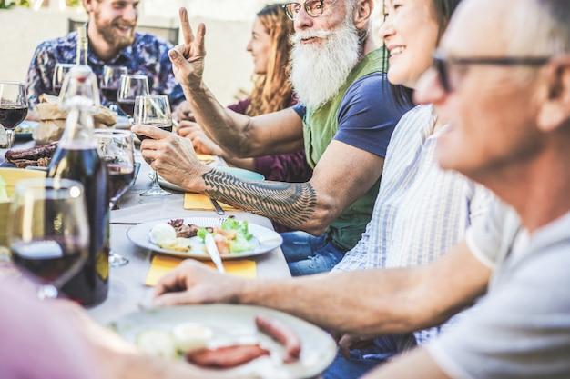 Glückliche familie, die wein am grillabendessen im backyar im freien isst und trinkt Premium Fotos