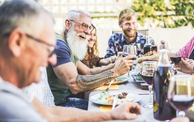 Glückliche familie, die wein beim grillabendessen auf der terrasse im freien isst und trinkt Premium Fotos