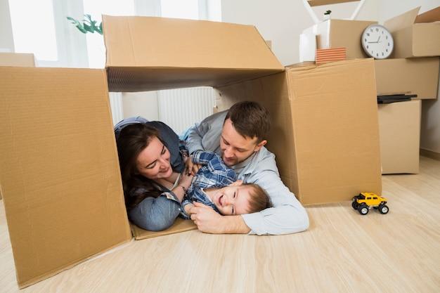 Glückliche familie, die zu hause innerhalb der pappschachtel liegt Kostenlose Fotos