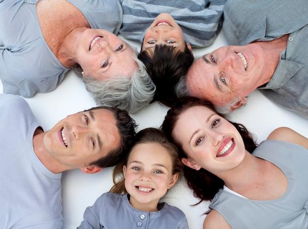 Glückliche familie, die zusammen auf boden mit köpfen liegt Premium Fotos