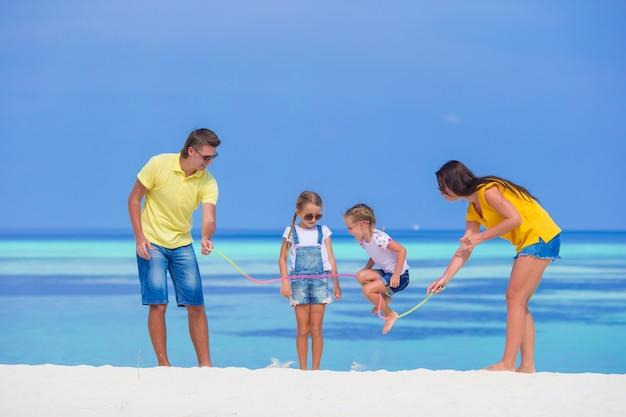 Glückliche familie, die zusammen auf weißem strand spielt Premium Fotos