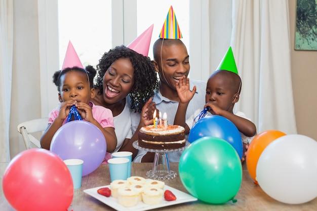Glückliche familie, die zusammen einen geburtstag am tisch feiert Premium Fotos