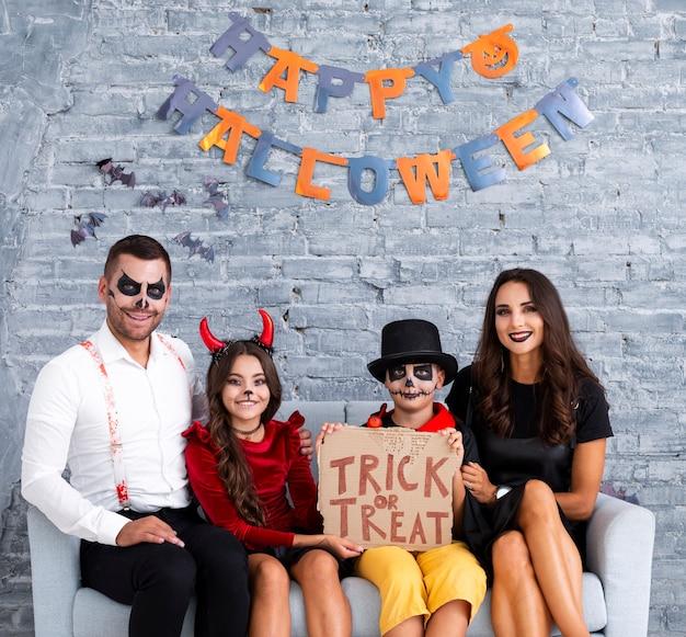 Glückliche familie, die zusammen für halloween aufwirft Kostenlose Fotos