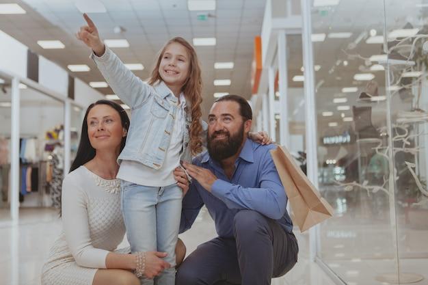 Glückliche familie, die zusammen im einkaufszentrum kauft Premium Fotos