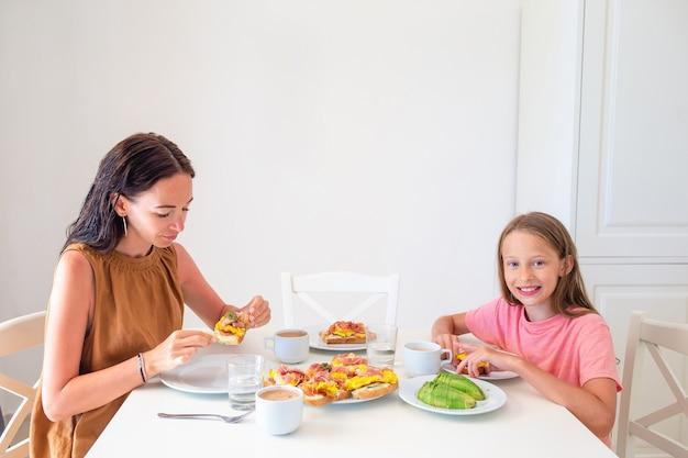 Glückliche familie, die zusammen in der küche frühstückt Premium Fotos