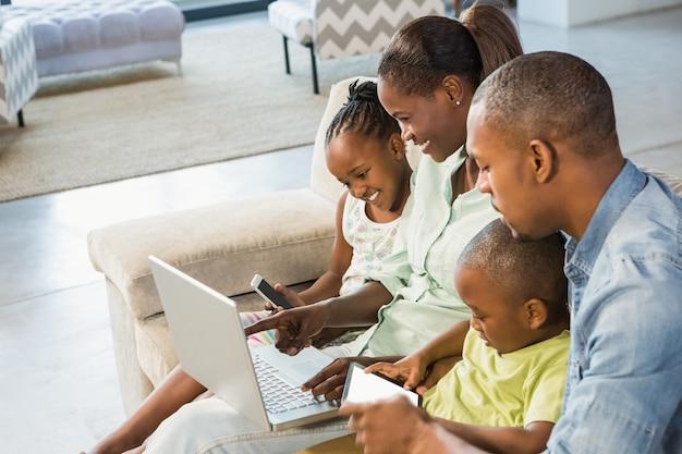 Glückliche familie, die zusammen technologie im wohnzimmer verwendet Premium Fotos