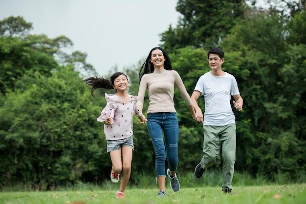 Glückliche familie hat spaß mutter, vater und tochter laufen in park. Kostenlose Fotos