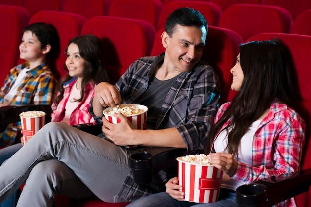 Glückliche familie im kino sitzen Kostenlose Fotos
