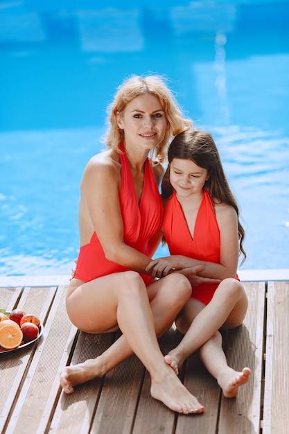 Glückliche familie im urlaub. mutter und tochter in badeanzügen sitzen am pool. Kostenlose Fotos
