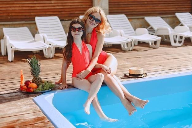 Glückliche familie im urlaub. mutter und tochter in badeanzügen und sonnenbrille sitzen am pool. Kostenlose Fotos