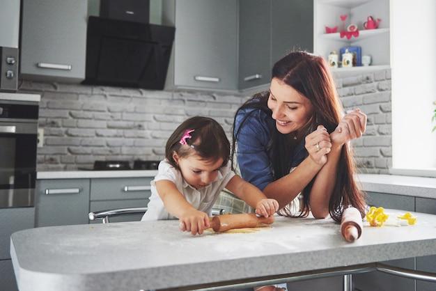 Glückliche familie in der küche. holiday food konzept. mutter und tochter bereiten den teig vor und backen kekse. glückliche familie bei der herstellung von keksen zu hause. hausgemachtes essen und kleiner helfer Kostenlose Fotos