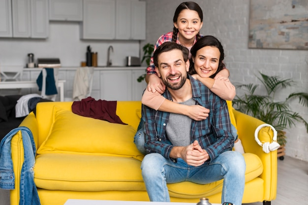 Glückliche familie in einem haufen und vater, die auf sofa sitzen Premium Fotos