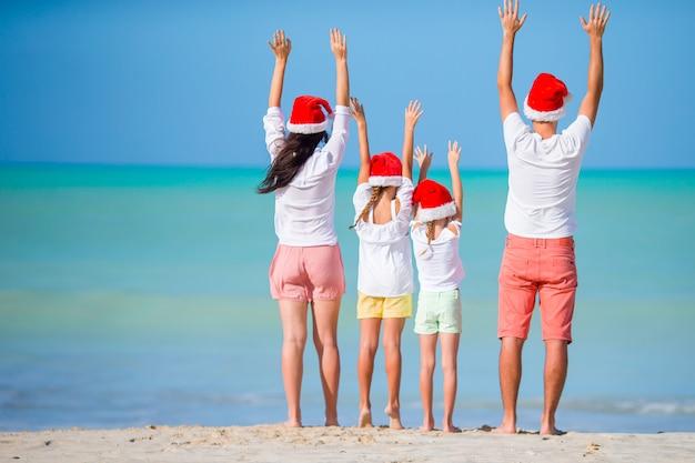 Glückliche familie in roten sankt-hüten auf einem tropischen strand weihnachtsferien feiernd Premium Fotos