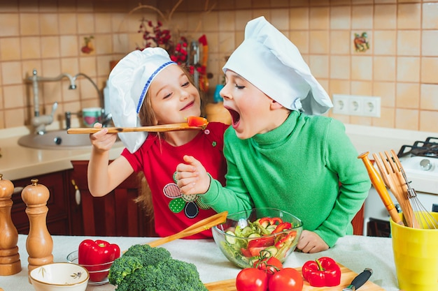 Glückliche familie lustige kinder bereiten den frischen gemüsesalat in der küche vor Kostenlose Fotos