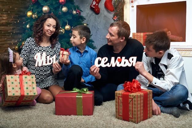 Glückliche familie: mama, papa und drei kinder am kamin für die winterferien. heiligabend und silvester. auf dem foto russische buchstaben des wortes: wir sind eine familie. Premium Fotos