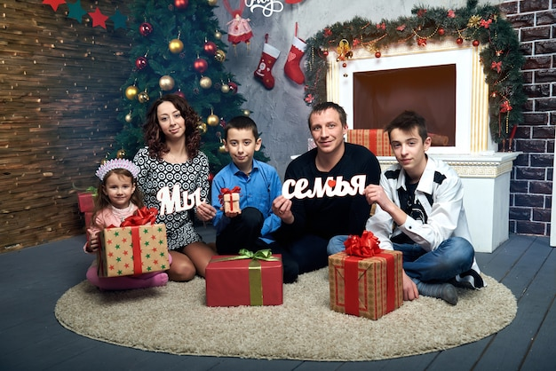 Glückliche familie: mama, papa und drei kinder am kamin für die winterferien. heiligabend und silvester. Premium Fotos