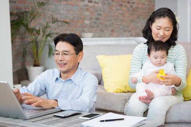 Glückliche familie mit babytochter im wohnzimmer, das rechnungen zählt Premium Fotos
