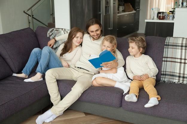 Glückliche familie mit dem kinderlesebuch, das zusammen auf sofa sitzt Kostenlose Fotos