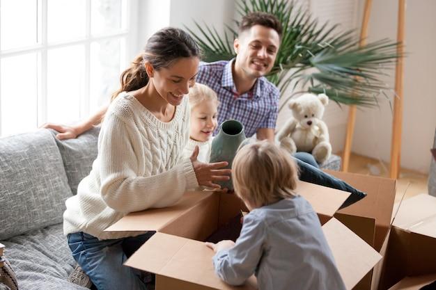 Glückliche familie mit den kindern, die die kästen auspacken, die in neues haus umziehen Kostenlose Fotos