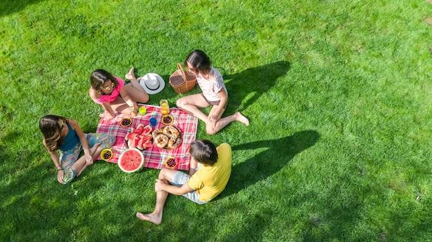 Glückliche familie mit den kindern, die picknick im park haben, eltern mit den kindern, die auf gartengras sitzen und draußen gesunde mahlzeiten essen Premium Fotos