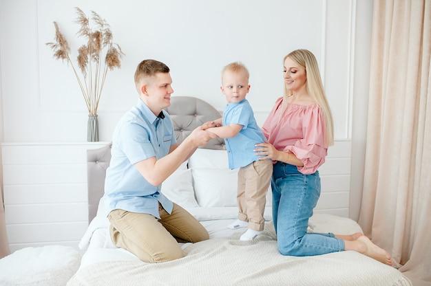 Glückliche familie mit einem niedlichen baby. mama, papa, sohn spielen auf dem bett in einem hellen, gemütlichen raum zu hause. Premium Fotos