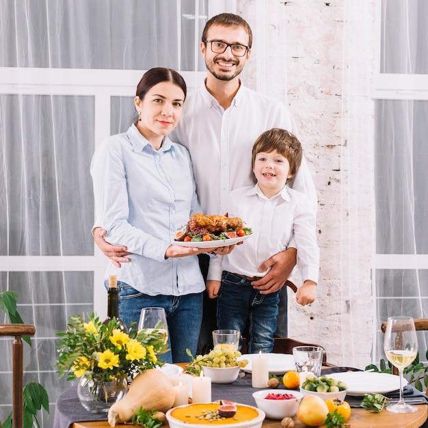 Glückliche familie mit gebackenem huhn bei tisch Kostenlose Fotos