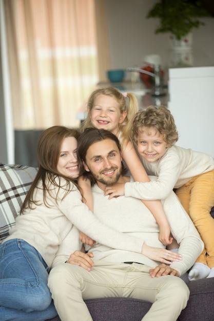 Glückliche familie mit kindern auf dem sofa, das kamera, porträt betrachtet Kostenlose Fotos