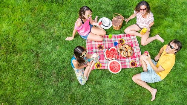 Glückliche familie mit kindern, die picknick im park haben, eltern mit kindern, die auf gartengras sitzen und gesunde mahlzeiten im freien essen Premium Fotos